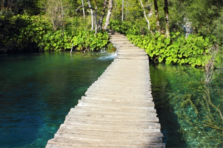 Wooden Path in Plitvice Lakes Park, for crossing over an emerald colored water surface of the lakes.  photo