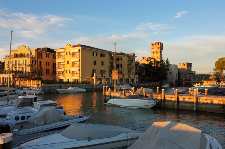garda: Sunset view of the luxury yacht port in Sirmione on Lake Garda in Italy.