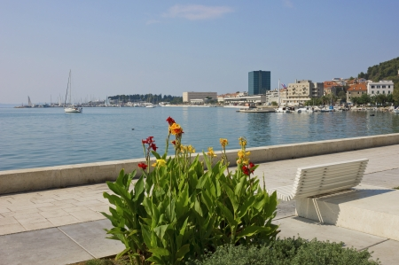 A panoramic view of The Riva Waterfront in Split, Croatia with a colorful flowers, a bench and sailboats in the marina. photo