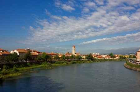 campanille: Panoramic view of Adige river with the famous basilica di San Zeno in Verona, Italy in a bright sunny day with beautiful white clouds in the distance over blue sky.