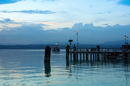 Peaceful evening on Lago di Garda in Italy, with Jetty pier in Sirmione and the last ferry boat for the day. Romantic italian summer night theme. photo