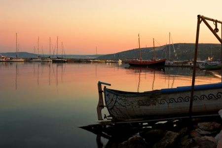 balchik: Tranquil sunset scene in a peaceful evening with fishing boats docked in the harbor. Northern Black Sea coast the port of Balchik. Stock Photo