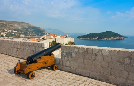 campanille: Panoramic view from the top of the citadel toward the old part of Dubrovnik in Dalmatia, Croatia with old cannon and island Lokrum at the background in a bright sunny day  Stock Photo