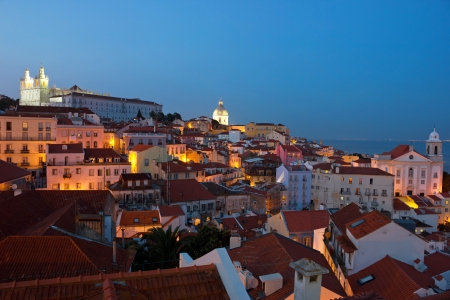Summer evening panoramic view of the old part of Lisbon Alfama in Portugal, with the street lights glowing in the dark