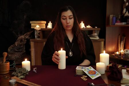 Witch is fortune teller with brown hair in black mantle holding white candle. Magical ritual. Tarot cards, white candles. Occult, esoteric, divination and wicca concept. Mystic and vintage background.