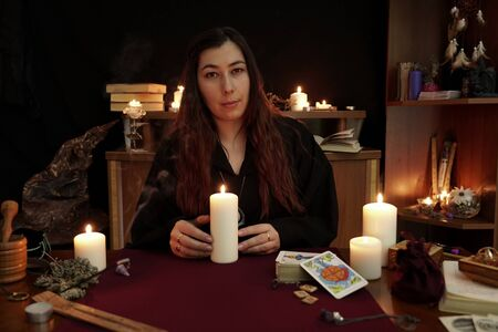 Witch is fortune teller in black robe holding white candle. Magical ritual. Tarot cards, white candles. Occult, esoteric and divination concept. Mystic and vintage background. Woman looks in camera.