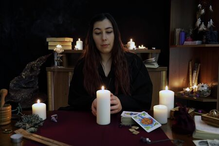 A witch is fortune teller in black mantle speaks a white candle. Magical ritual. Tarot cards, white candles. Occult, esoteric and divination concept. Mystic and vintage background. Cold tone.