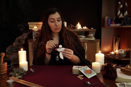 A witch is fortune teller in black mantle hold voodoo doll with red threads. Magical ritual. Tarot cards, white candles on table. Occult, esoteric, divination and Wicca concept. Mystic background.