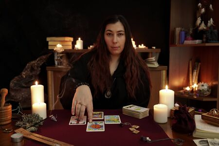 Witch is fortune teller in black robe points to good luck card. Magical ritual. Tarot cards, white candles, aroma stick, ancient book and runes. Occult, esoteric, divination concept. Mystic background