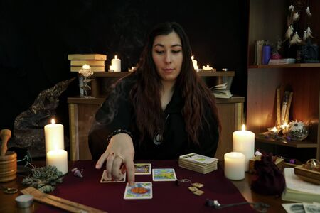 Witch is fortune teller in black mantle lays out tarot cards. Magical ritual. Tarot cards, white candles, aroma stick, ancient book and runes. Occult, esoteric, divination concept. Mystic background. Imagens