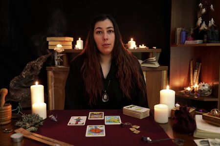 Portrait of witch in a black robe. Magical ritual. Tarot cards, white candles, aroma stick, ancient book and runes on table. Occult, esoteric, divination concept. Mystic background.