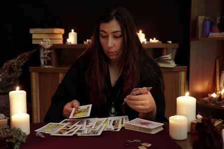 Witch is fortune teller in black mantle arranges tarot cards on table. Magical ritual. White candles, aroma stick, ancient books, runes and amulets. Esoteric and divination concept. Mystic background.