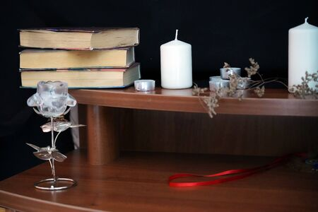 Composition of esoteric objects. White candles, wormwood, glass flower, ancient books on a wooden table on black background. Occult, esoteric, divination and wicca concept. Mystic background.