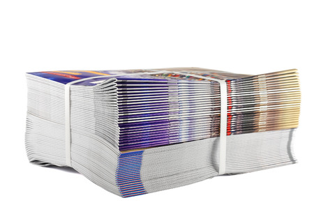 Pile of bundled magazines isolated on white background photo