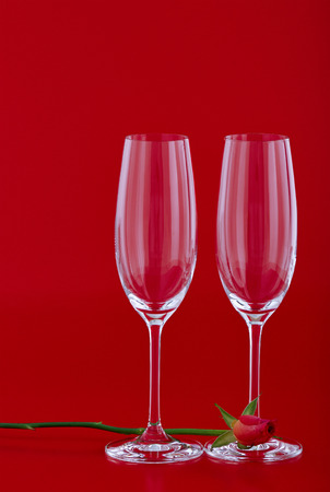Two wine glasses with rose flower over red background photo