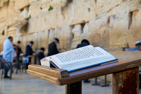 Western Wall also known as Wailing Wall in Jerusalem. The Bible Book in the foreground. Stock Photo