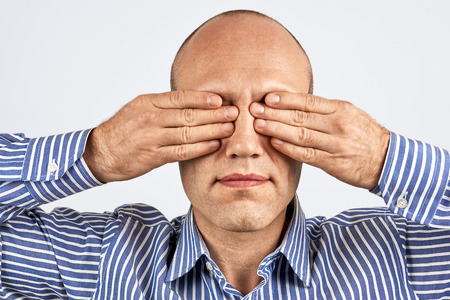 tightly: Man with eyes tightly closed with hands