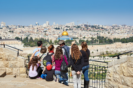 Jerusalem, Israel - April 18, 2015: The guide shows the Jerusalem Old City view to the tourists. Mount of Olives is a famous and sacred Christian's place with a fantastic view to the Old City of Jerusalem. Editoriali