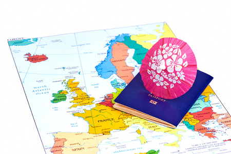cocktail umbrella: Passport and map of Europe with cocktail umbrella. Travel concept.