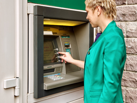 operates: Business woman operates an ATM on the street