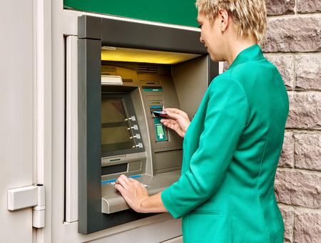 operates: Donna di affari che opera un bancomat per la strada Archivio Fotografico