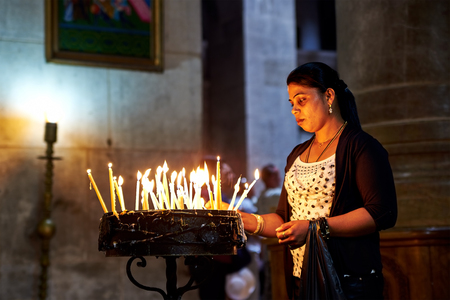 anoint: Jerusalem, Israel - June 06, 2015: Prayers lighting candles in the Holy Sepulchre Church in Jerusalem. The Holy Sepulchre Church is the most sacred place for all Christians in the world. Editorial