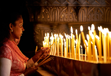 holy land: Jerusalem, Israel - June 06, 2015: Prayers lighting candles in the Holy Sepulchre Church in Jerusalem. The Holy Sepulchre Church is the most sacred place for all Christians in the world. Editorial
