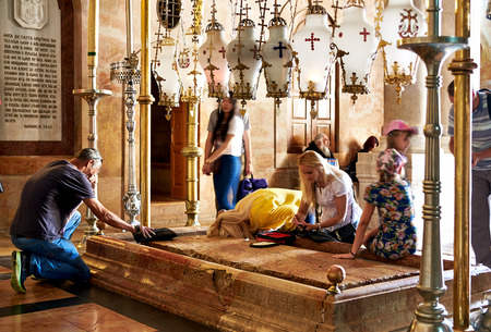 sepulchre: Jerusalem, Israel - June 06, 2015: Prayers at the Stone of Anointing in the Holy Sepulchre Church in Jerusalem. The Holy Sepulchre Church is the most sacred place for all Christians in the world.