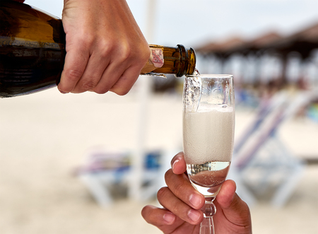 champaigne: Champagne pouring into the wineglass on the beach