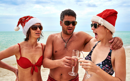 bikini couple: Handsome man and two beautiful girls in bikini and Christmas Santa hat drinking champagne at the beach Stock Photo
