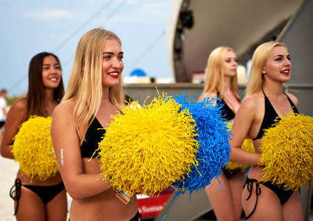 girl sport: Lazurne, Ukraine - August 23, 2015: Beautiful cheerleader girls dancing at the festival Crazy People of sport and music on the Black Sea beach. The festival gathers a lot of people and celebrities. Editorial