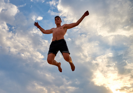 flying man: Lazurne, Ukraine - August 23, 2015: Flying man over beautiful sky at the youth festival Crazy Days of sport and music on the Black Sea beach. The festival gathers a lot of people. Trampoline sport. Editorial