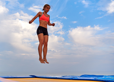 expresion corporal: Lazurne, Ukraine - August 23, 2015: Flying girl over beautiful sky at the youth festival Crazy Days of sport and music on the Black Sea beach. The festival gathers a lot of people. Trampoline sport.