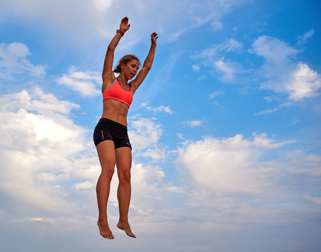 body expression: Lazurne, Ukraine - August 23, 2015: Flying girl over beautiful sky at the youth festival Crazy Days of sport and music on the Black Sea beach. The festival gathers a lot of people. Trampoline sport.