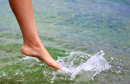 hot spring: Woman splashes the sea water with her leg at the beach