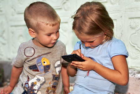 children play: Children boy and girl play with smartphone Stock Photo