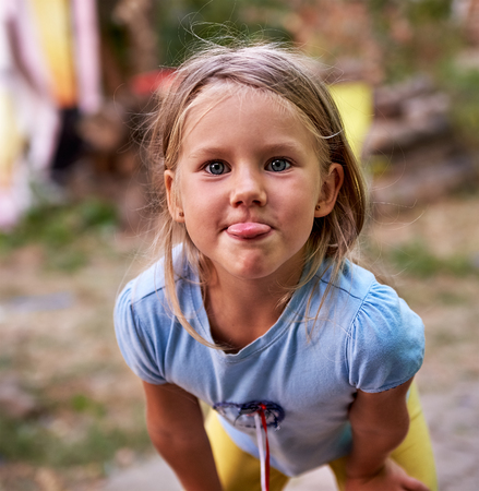 teases: Little girl outdoors teases and puts out her tongue