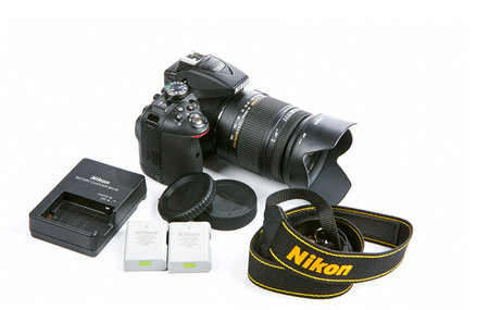sigma: Kiev, Ukraine - November 02, 2015: Nikon D5300 DSLR Camera with Zoom Sigma 18-250 mm OS HSM Macro Lens isolated on white background. Full set with batteries, charger, strap and caps.