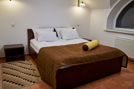 bolster: Double bed with pillows and ergonomic bolster in bedroom