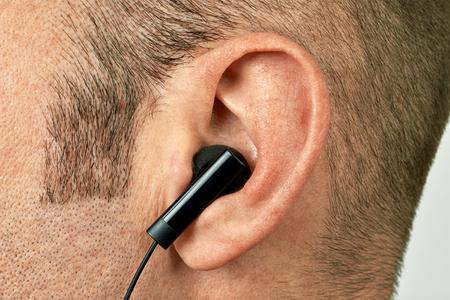 earphone: Ear with black earphone closeup