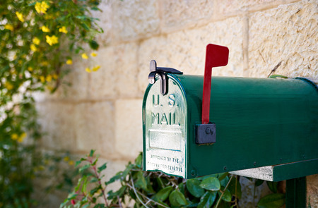 Green US post mail letter box with red flag raised up