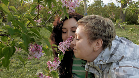 sniffing: Two pretty girls or young women sniffing smelling at lilac flowers in the green park in spring. Togetherness and friendship positive springtime concept.
