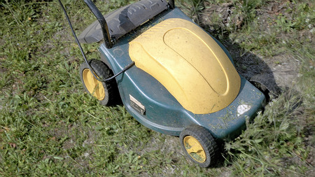 mowing grass: Mowing grass in the garden with electrical mowing machine. Summer gardening recreation concept.