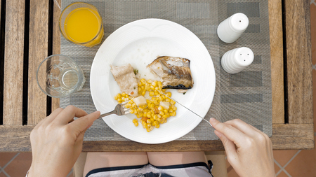 devouring: The lady sitting at the wooden table is devouring a plate with meals. The lady is using cutlery utensils to cut her dish meal in small bites. Top view. Unusual POV.