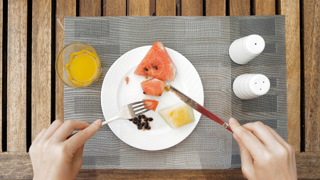 devouring: The lady sitting at the wooden table is devouring a plate with meals. The lady is using cutlery utensils to cut her fruit dish meal in small bites. Top view. Unusual POV. Stock Photo