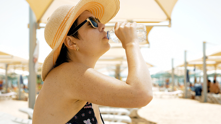 quenching: A female is quenching her thirst by drinking water at the beach. On a hot summer day one needs to stay hydrated. Water helps you stay healthy.