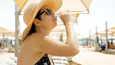 sediento: Una hembra está apagando su sed por el agua potable en la playa. En un día caluroso de verano que se necesita para mantenerse hidratado. El agua ayuda a mantenerse sano.