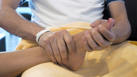 ligaments: A man is showing a kind gesture by massaging someones foot. Massage is great way to feel relaxed. Massaging involves applying pressure.