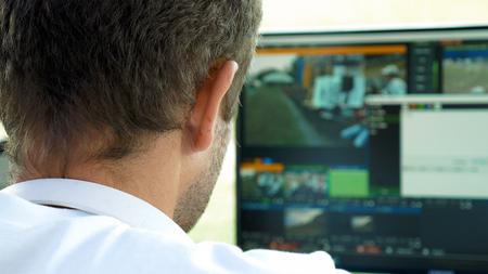 Vidéo éditeur de diffusion avec un casque en regardant une action sur le moniteur. Direct processus de diffusion TV.