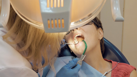 dental calculus: Woman at the dentist clinic office gets dental medical examination and treatment. Odontic and mouth health is important part of modern human life that dentistry help with.